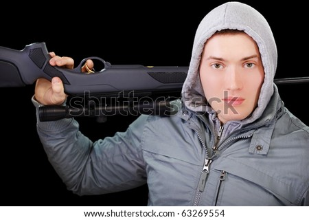 portrait of handsome young man in gray jacket with hood holding sniper rifle in hands on black - stock photo