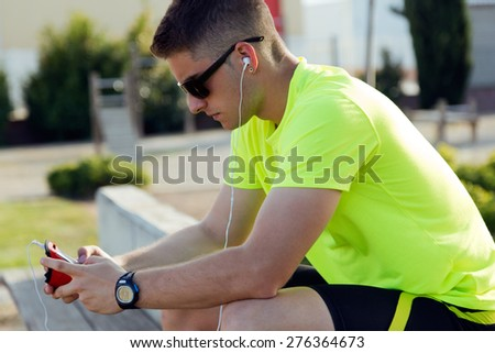Portrait of handsome young man listening to music after running. - stock photo