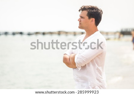 Portrait of handsome young man looking on the horizon at sea - stock photo