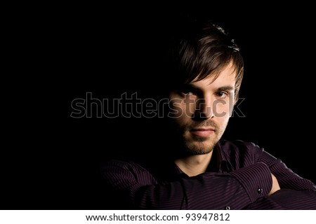 Portrait of handsome young man on a black background - stock photo