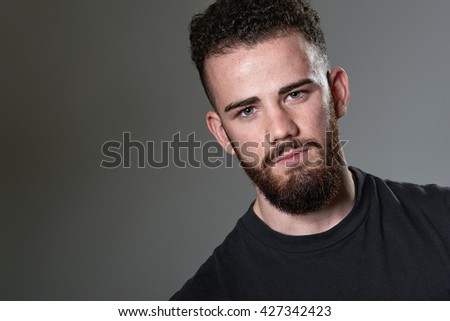 Portrait of handsome young man, on grey background - stock photo