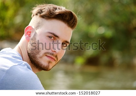 Portrait of handsome young man outdoors in nature, looking in camera - stock photo