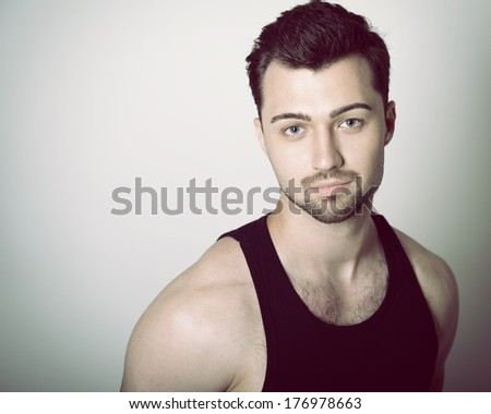 Portrait of handsome young man over black, toned - stock photo