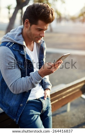 Portrait of handsome young man sending a text message while standing outside, male student reading text messages outdoors, stylish brunette hipster using cell phone at sunny evening, flare sunshine - stock photo