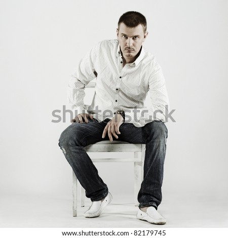 Portrait of handsome young man sitting on a chair - stock photo