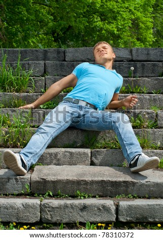 Portrait of handsome young man sitting on the stairway in the park and enjoying the sun - stock photo