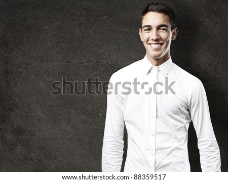 portrait of handsome young man smiling against a grunge background - stock photo