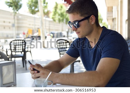 Portrait of handsome young man using his mobile phone in the street.  - stock photo
