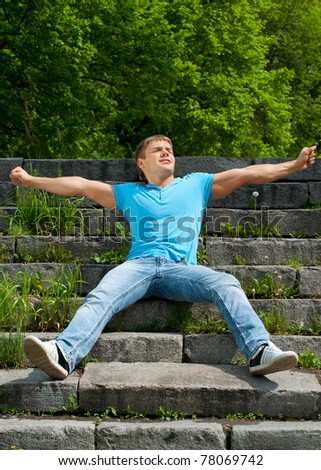 Portrait of handsome young man wearing casual sitting on the stairs in the park and stretching - stock photo