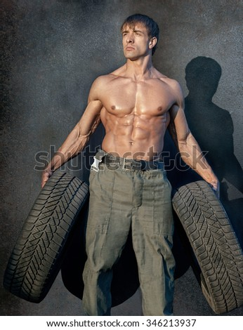 Portrait of handsome young muscular shirtless man with rubber tyres - stock photo