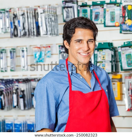 Portrait of handsome young worker in red apron smiling at hardware shop - stock photo