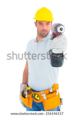 Portrait of handyman using power drill on white background - stock photo