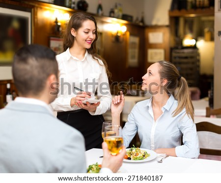Portrait of happy adults having dinner and respectful waiter - stock photo