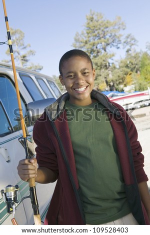 Portrait of happy African American boy with a fishing rod - stock photo
