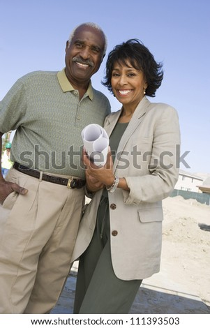 Portrait of happy African American couple holding blueprint at an empty land - stock photo