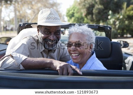 Portrait of happy African American couple in car - stock photo