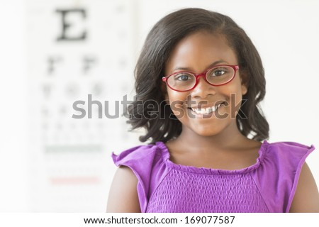 Portrait of happy African American girl wearing glasses against eye chart in clinic - stock photo