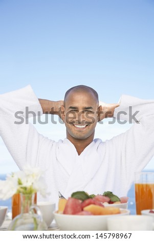 Portrait of happy African American man in bathrobe sitting at breakfast table - stock photo