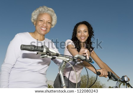 Portrait of happy African American mother and daughter sitting on bicycle against blue sky - stock photo