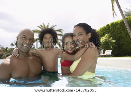 Portrait of happy African American parents with children in swimming pool - stock photo