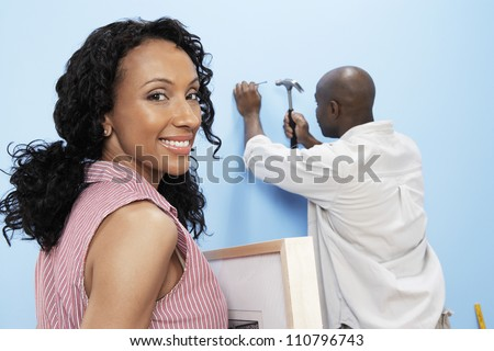 Portrait of happy African American woman holding picture frame with man hammering nails into wall - stock photo