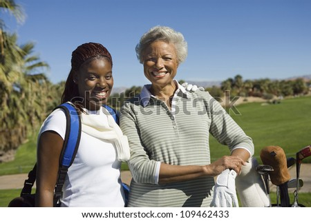Portrait of happy African American woman with granddaughter at golf course - stock photo
