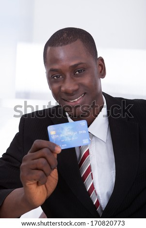 Portrait Of Happy African Businessman Holding Credit Card - stock photo