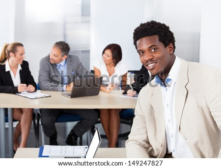 Portrait Of Happy African Businessman Sitting In Front Of Colleagues - stock photo