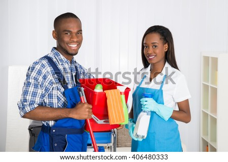 Portrait Of Happy African Male And Female Janitors - stock photo