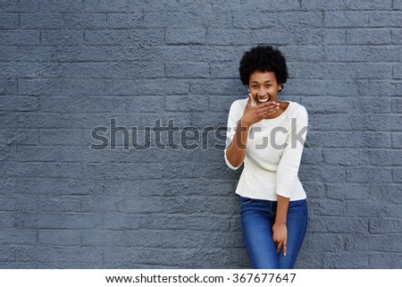 Portrait of happy african woman covering her mouth and laughing against a gray wall  - stock photo