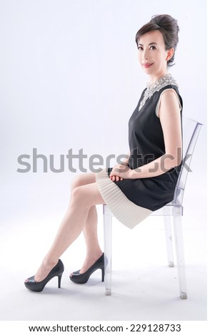 Portrait of happy aged woman sitting chair  - stock photo