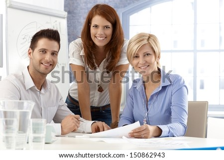 Portrait of happy and attractive office team, smiling at camera. - stock photo