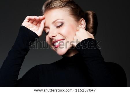 portrait of happy and glamor female against dark background - stock photo