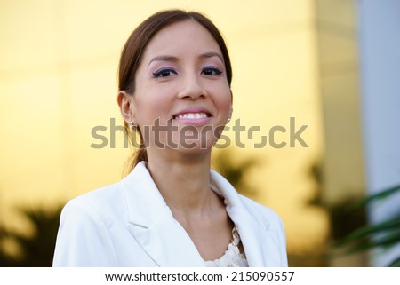 Portrait of happy and self confident latina businesswoman in tailleur smiling at camera in office  - stock photo