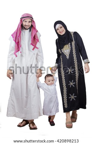 Portrait of happy Arabic family walking in the studio while holding hands and smiling at the camera - stock photo