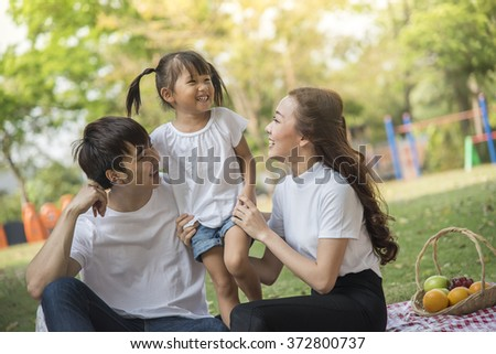 Portrait Of Happy Asian Family In Garden - stock photo