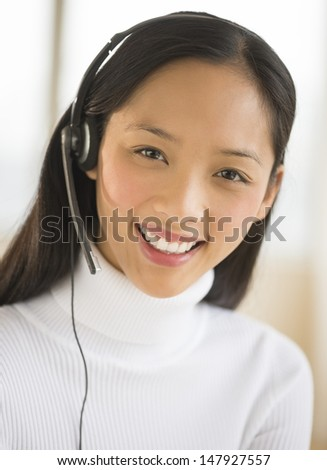 Portrait of happy Asian female customer service representative wearing headset - stock photo