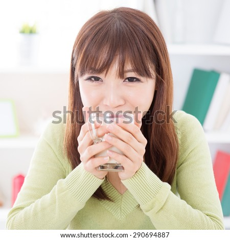 Portrait of happy Asian girl drinking soymilk as breakfast. Young woman indoors living lifestyle at home. - stock photo