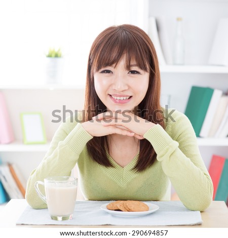 Portrait of happy Asian girl eating breakfast. Young woman indoors living lifestyle at home. - stock photo