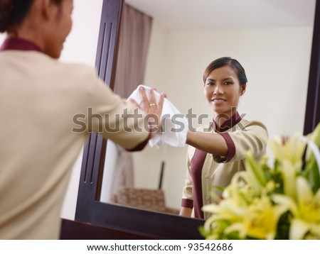 Portrait of happy Asian housekeeper at work in luxury hotel room and smiling at camera - stock photo