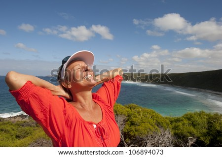 Portrait of happy attractive looking mature middle aged woman joyful laughing, isolated with sunshine on face, ocean, sly and coastline as background and copy space. - stock photo