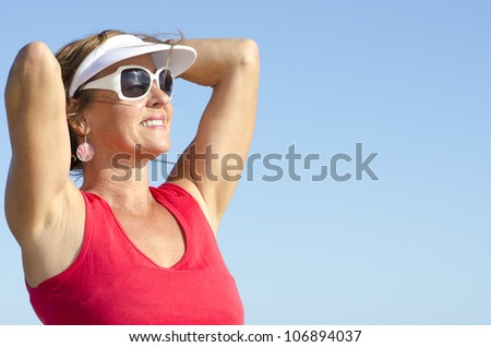 Portrait of happy attractive looking middle aged woman joyful laughing, isolated with sunshine on face and sky as background and copy space. - stock photo