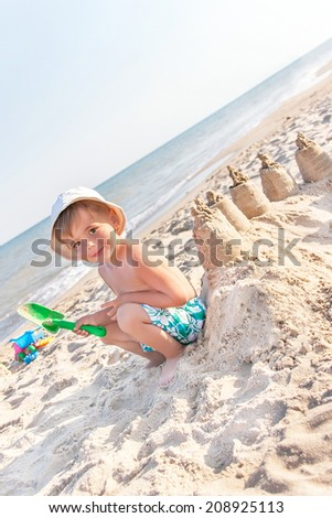 Portrait of happy baby (boy) is building sand castle by toy shovel at the beach. Caucasian kid (child) is smiling and enjoying serene ocean in the sunny summer day. Copy space. Outdoor, close up.   - stock photo