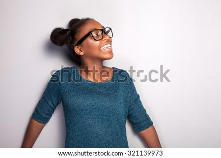 Portrait of happy beautiful african young girl with toothy smile. Teenage girl posing in studio, wearing fashionable eyeglasses. - stock photo
