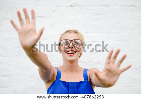 Portrait of happy beautiful blonde girl throws up her hands in grabbing move, closeup on white background - stock photo