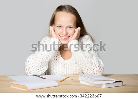 Portrait of happy beautiful casual caucasian girl wearing white knitted sweater, sitting at the desk, doing homework, studying, friendly smiling, looking at camera, studio shot, gray background - stock photo