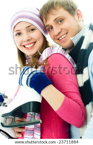 portrait of happy beautiful cheerful young couple going ice-skating - stock photo