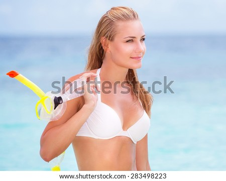Portrait of happy beautiful girl standing on seashore with a diving mask in hand, having fun on the beach, enjoying summer activities - stock photo