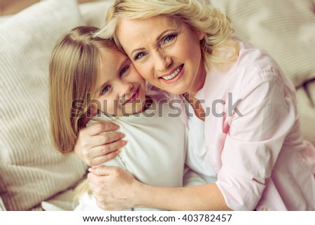 Portrait of happy beautiful granny and her granddaughter hugging, looking at camera and smiling - stock photo