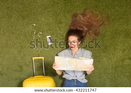 Portrait of happy beautiful tourist lady lying on green grass near yellow luggage and mobile or smart phone. Pretty woman looking at map or guide. - stock photo